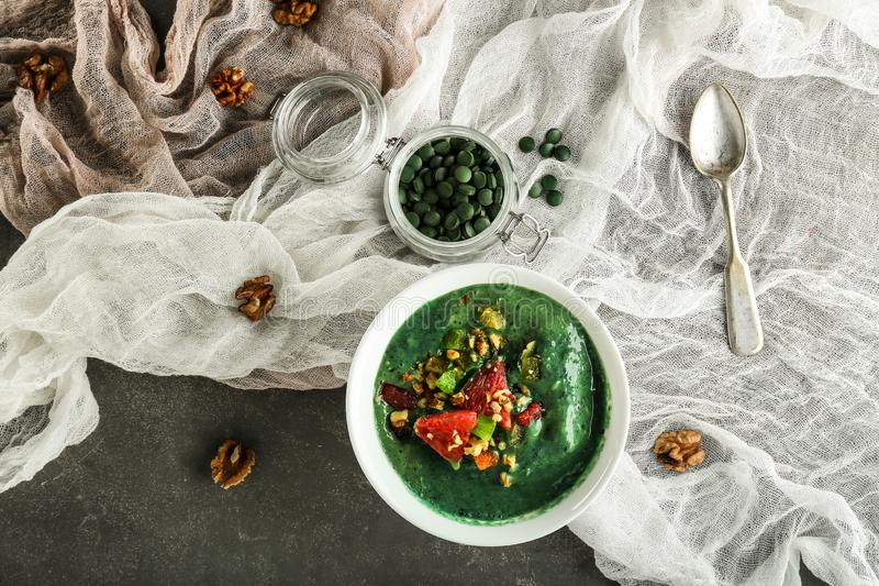 Bowl with spirulina smoothie on grey table royalty free stock image