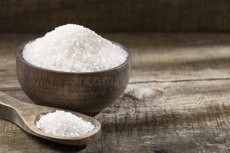 Refined white sugar in wooden bowl and spoon stock photo