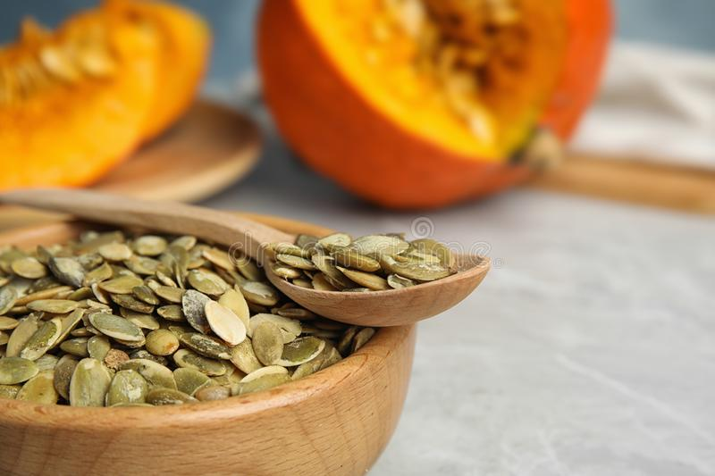 Bowl and spoon of raw pumpkin seeds on light grey table, closeup. Space for text stock photography