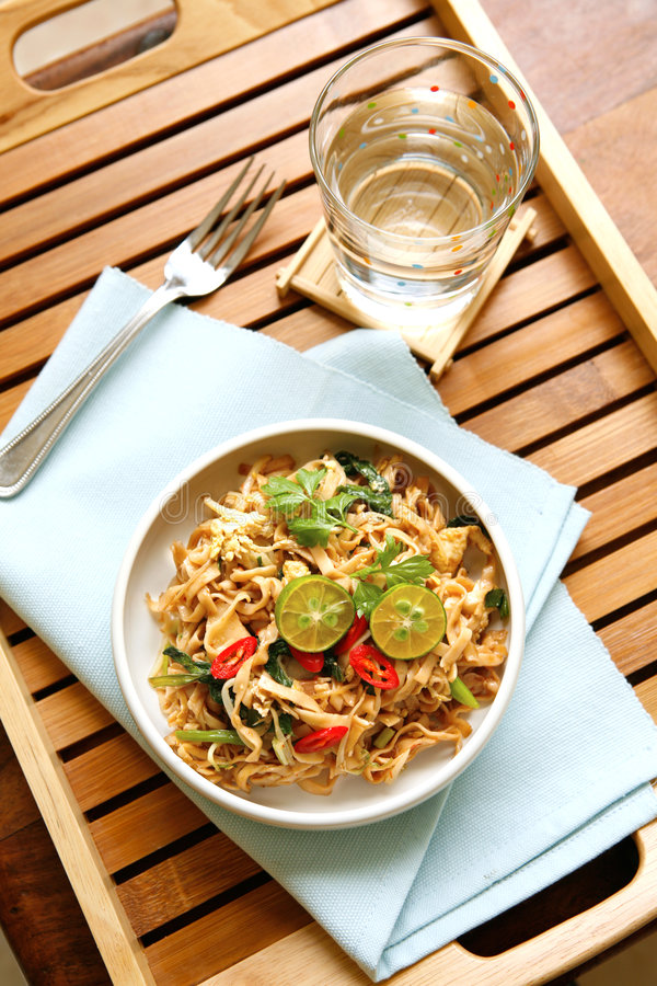 Bowl of stirfry noodle with fresh limes royalty free stock image