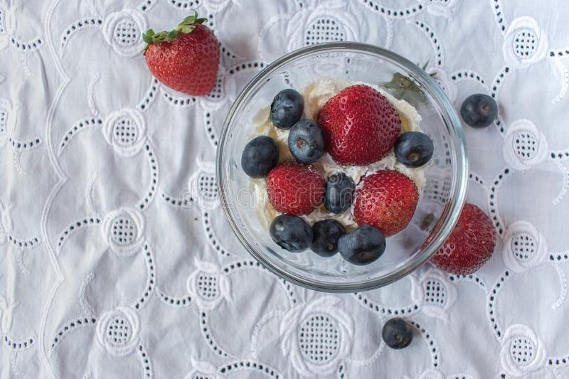 Bowl of strawberries and blueberries in whip cream on white linen tablecloth stock photos