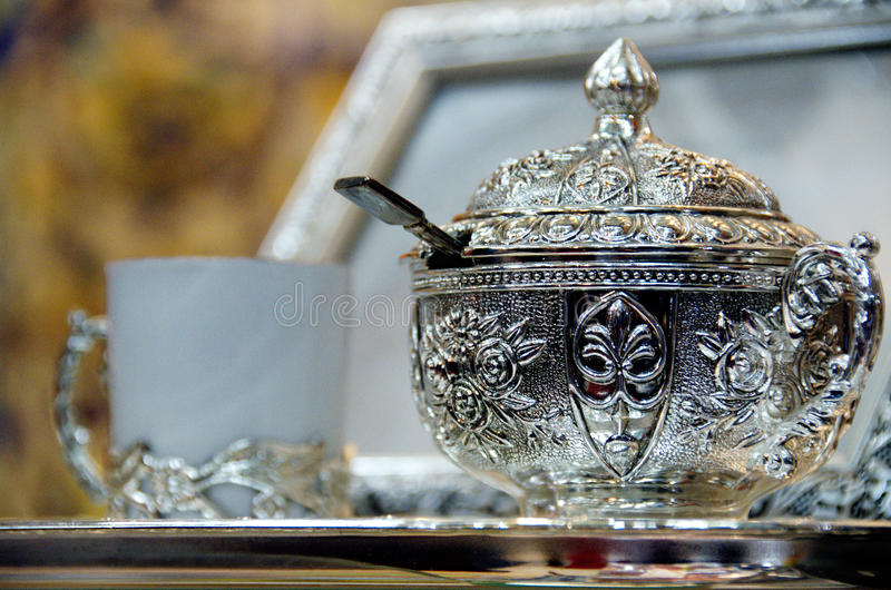 Bowl of sugar and coffee cup on a silver platter. Tunisisan bowl of sugar and coffee cup on a silver platter and silver picture frame in background stock photo