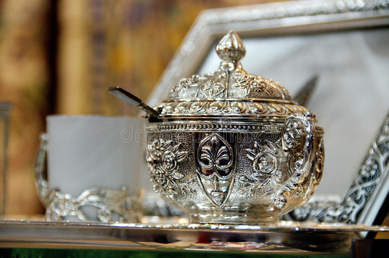 Bowl of sugar and coffee cup on a silver platter. Tunisisan bowl of sugar and coffee cup on a silver platter and silver picture frame in background royalty free stock images