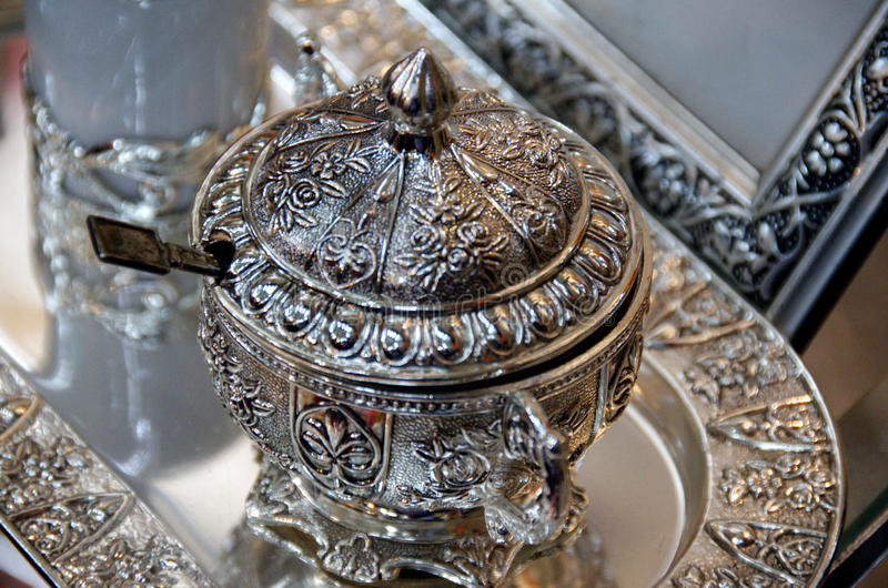 Bowl of sugar on a silver platter. Tunisisan bowl of sugar on a silver platter and silver picture frame in background stock photography