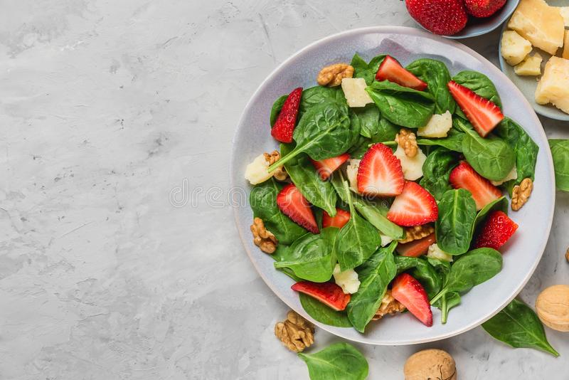 Bowl of summer spinach salad with strawberry, parmesan cheese and walnuts on concrete background. healthy diet food royalty free stock photo