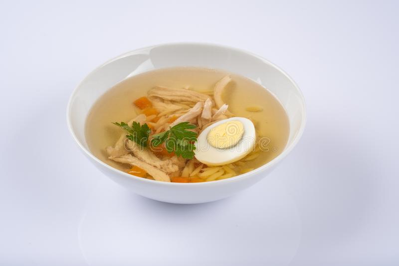 Bowl on a table with chicken herbs, gg and noodles soup royalty free stock image