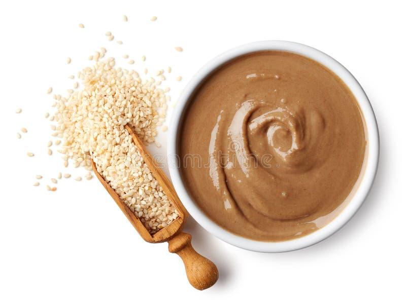 Bowl of tahini sauce and sesame seeds stock image