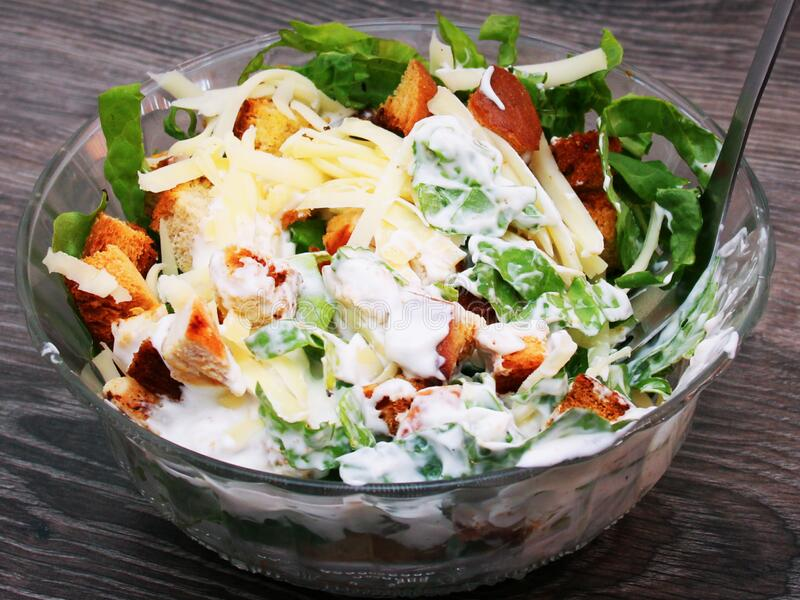Bowl of tasty Caesar salad. Bowl of fresh, tasty and healthy Caesar salad, home made, with fresh ingredients. Wooden rustic background royalty free stock photos