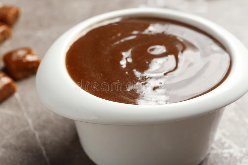 Bowl with tasty caramel sauce on table. Closeup stock images
