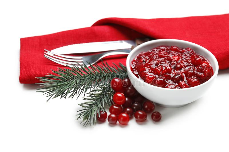 Bowl with tasty cranberry sauce and cutlery on white background stock images