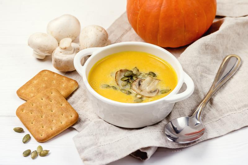 Bowl of Tasty Homemade Pumpkin Cream Soup decotated with Mushrooms and Pumpkin Seeds White Wooden Background Galette Horizontal royalty free stock images