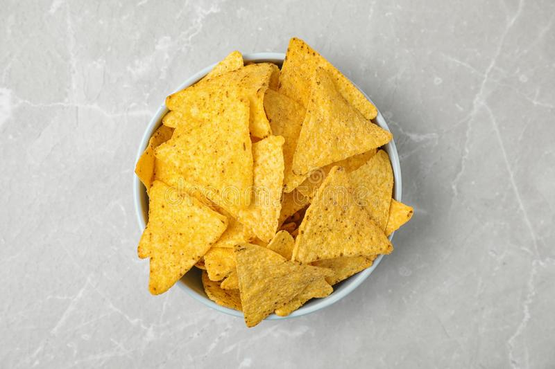 Bowl with tasty Mexican nachos chips on grey table royalty free stock images