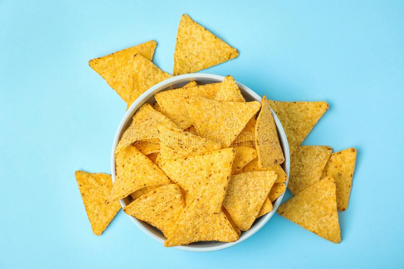 Bowl with tasty Mexican nachos chips on blue background, flat lay. Bowl with tasty Mexican nachos chips on light blue background, flat lay royalty free stock photography