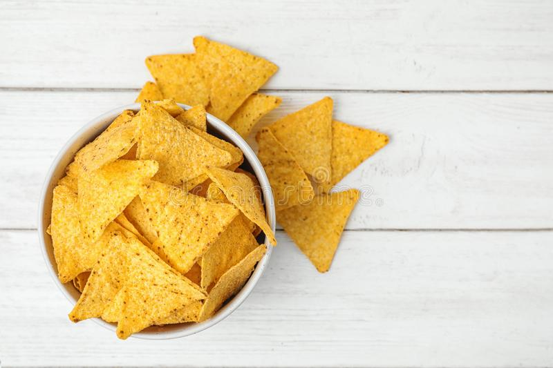 Bowl and tasty Mexican nachos chips on white wooden table. Space for text royalty free stock photos