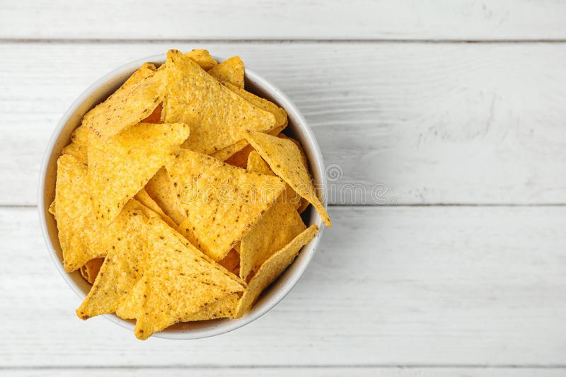 Bowl with tasty nachos chips on white wooden table, top view. Space for text. Bowl with tasty Mexican nachos chips on white wooden table, top view. Space for royalty free stock photo