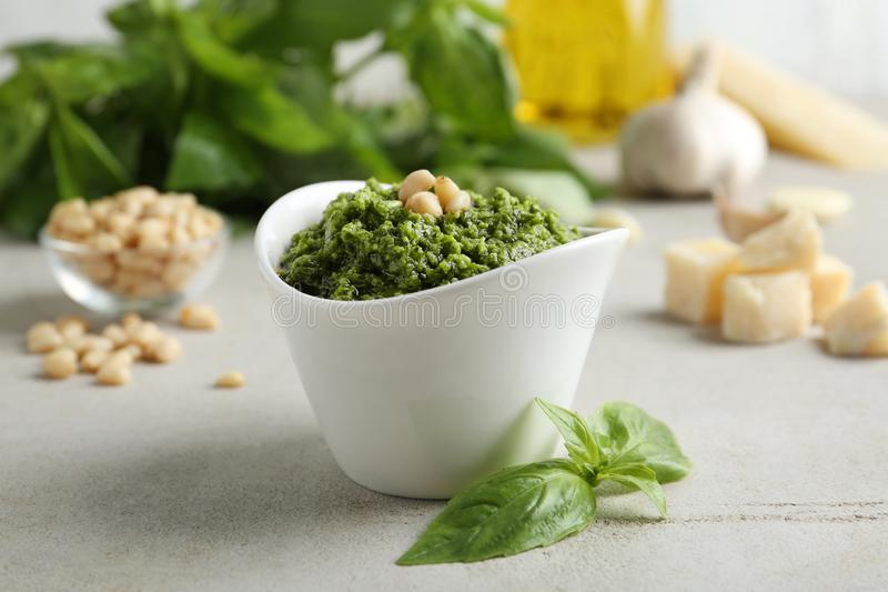 Bowl of tasty pesto sauce and ingredients. On light table stock photography