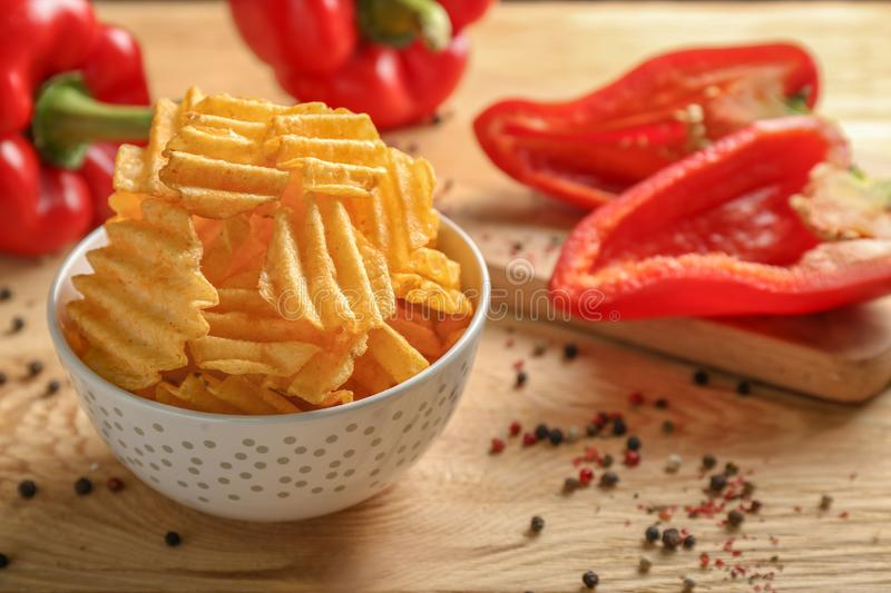 Bowl of tasty potato chips with paprika on wooden background royalty free stock image