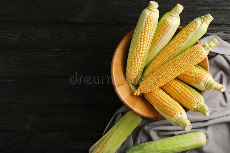 Bowl with tasty sweet corn cobs on wooden table royalty free stock images