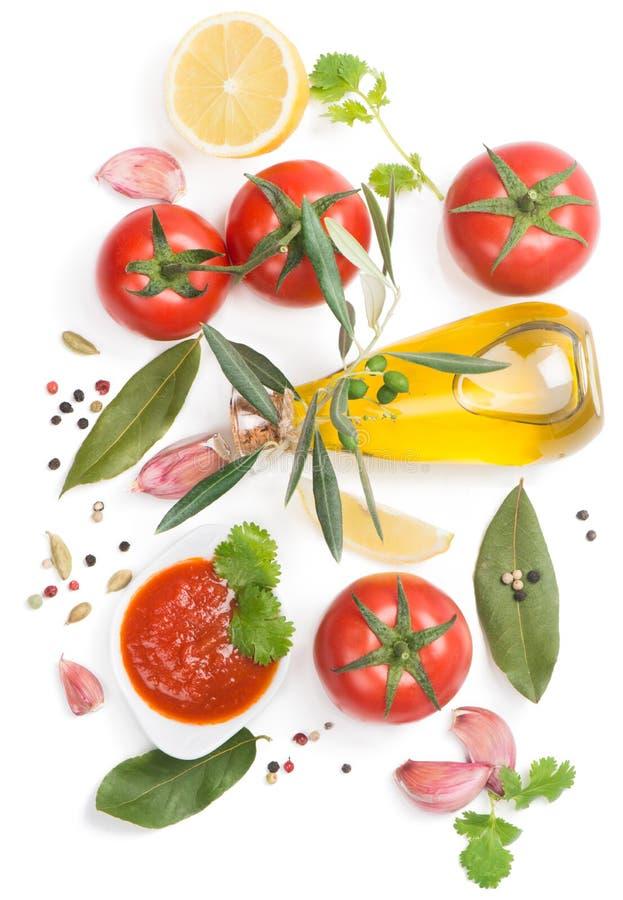Bowl of tomato sauce with fresh ingredients. Tomato sauce and the ingredients ( olive oil, spices, lemon, tomato), on white, top view stock photos