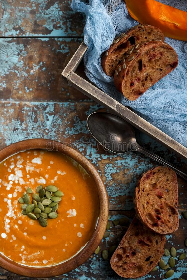 Bowl of traditional homemade pumpkin soup with seads, cream and bread on rustic wooden table stock photo