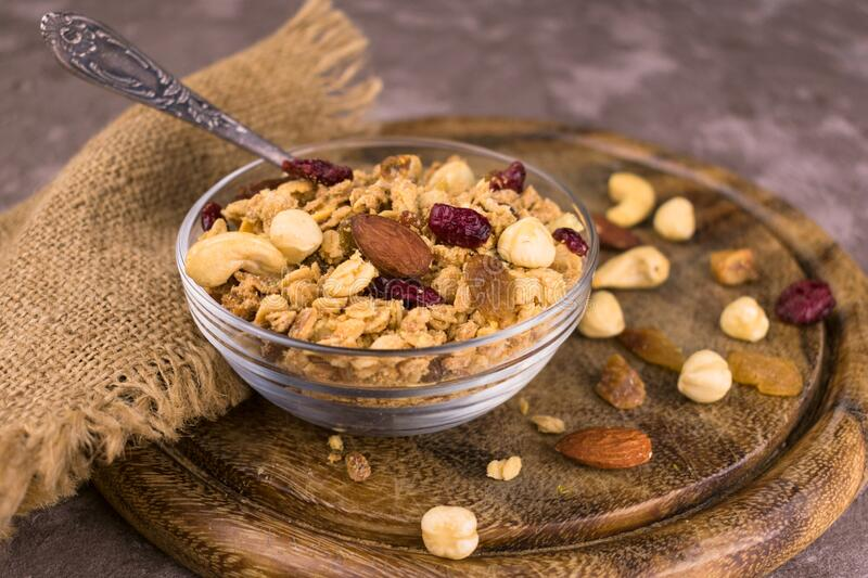 Bowl with useful and nutritious granola on a wooden board. Useful and nutritious granola on a wooden board stock photos