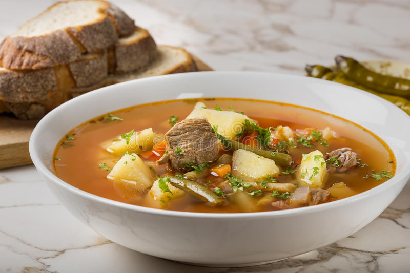 Bowl of vegetable beef soup with bread and hot chilli peppers in royalty free stock image