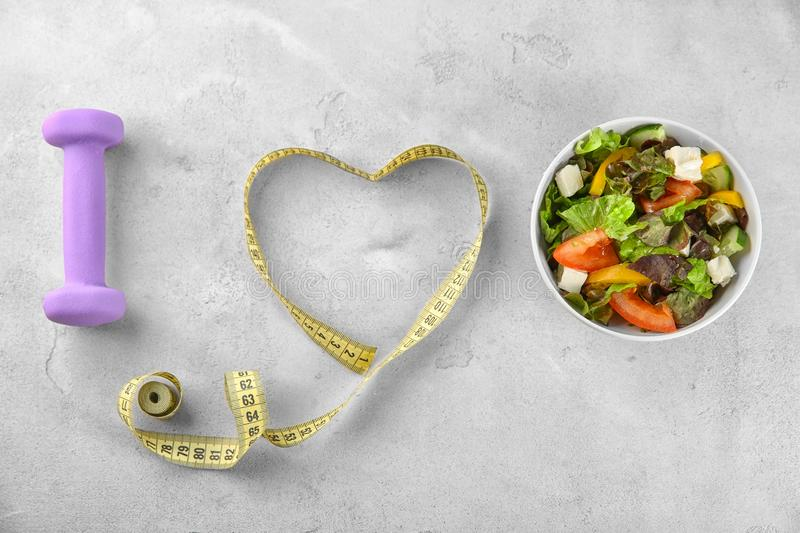 Bowl with vegetable salad, dumbbell and measuring tape on table. I love diet food royalty free stock photos