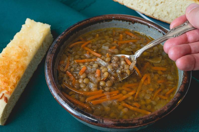 Bowl of vegetarian lentil soup with carrot, onion, and garlic. Served with delicious homemade cheese bread stock photo