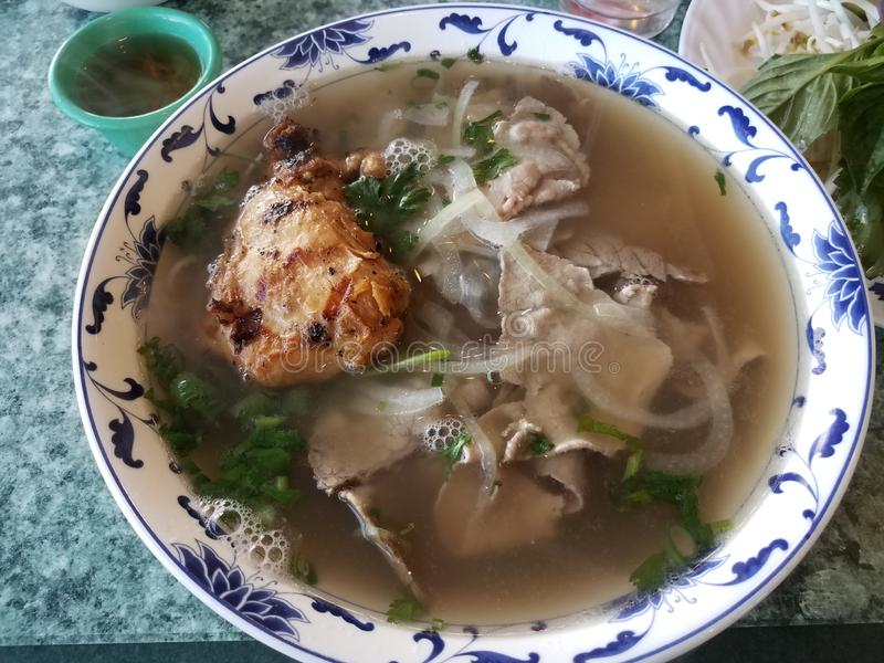 Bowl of Vietnamese soup with beef, chicken, and vegetables. Bowl of Vietnamese soup with beef, chicken, and onion and vegetables stock photo