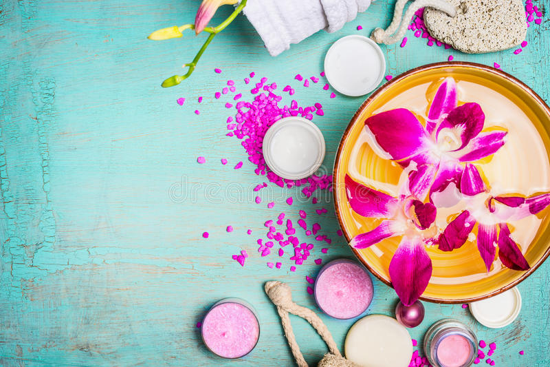 Bowl with water and pink orchid flowers with wellness and spa setting on turquoise blue background. Top view, close up stock image