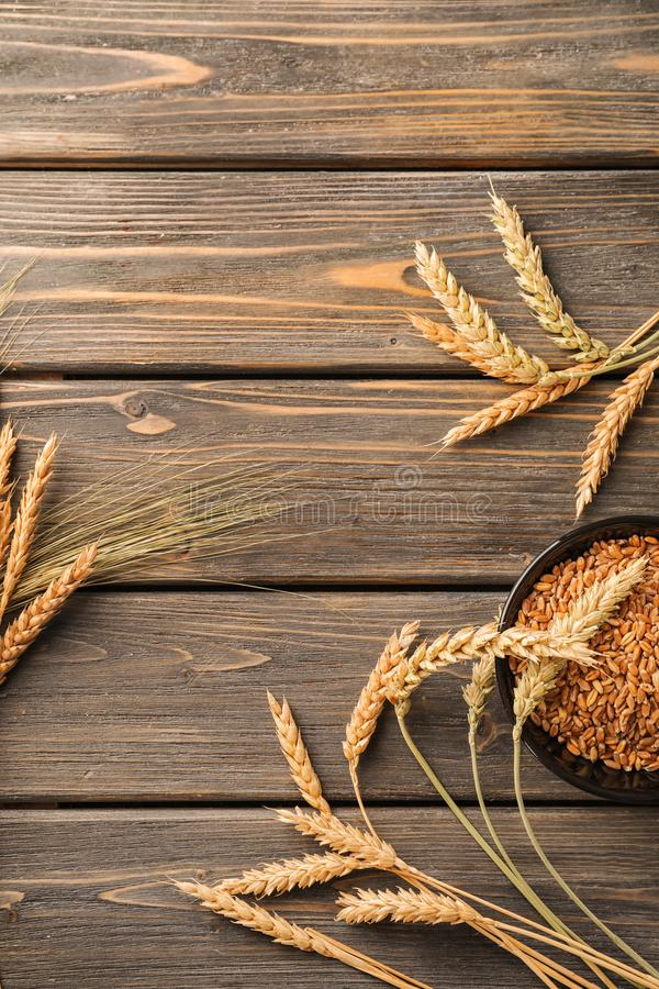 Bowl with wheat grains and spikelets on wooden table stock image