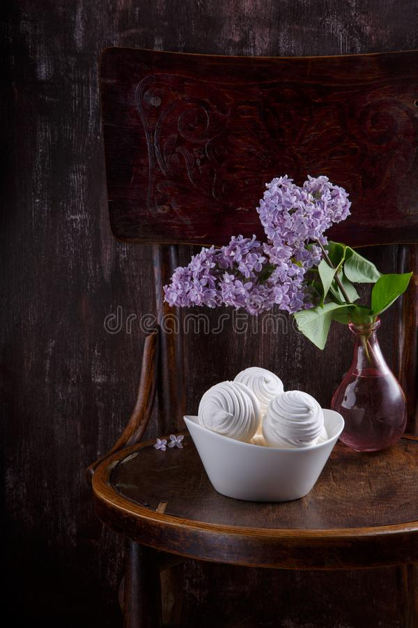 Bowl of white zephyr marshmallows and bouquet of lilac flowers on old vintage chair.  Still life on dark background stock photo