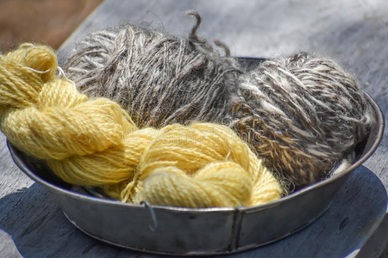 Bowl of Yellow and Gray Wool Yarn. A bowl of yellow and gray and white wool yarn ready to be knitted or crocheted into something special royalty free stock photography
