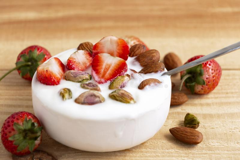 Bowl of yogurt, red fruit strawberry and dried fruit on the wood table. Yogurt made from milk fermented by added bacteria, often stock image