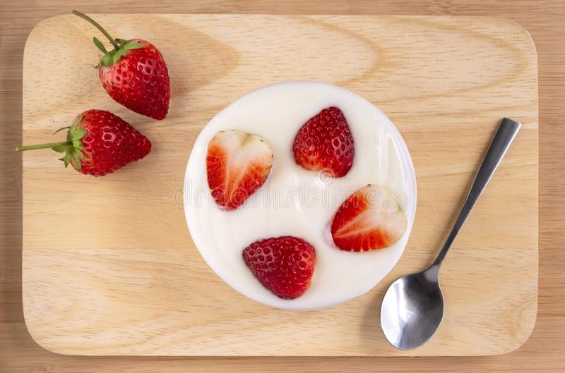 Bowl of yogurt and red fruit strawberry on the wood table. Yogurt made from milk fermented by added bacteria, often sweetened and royalty free stock photography