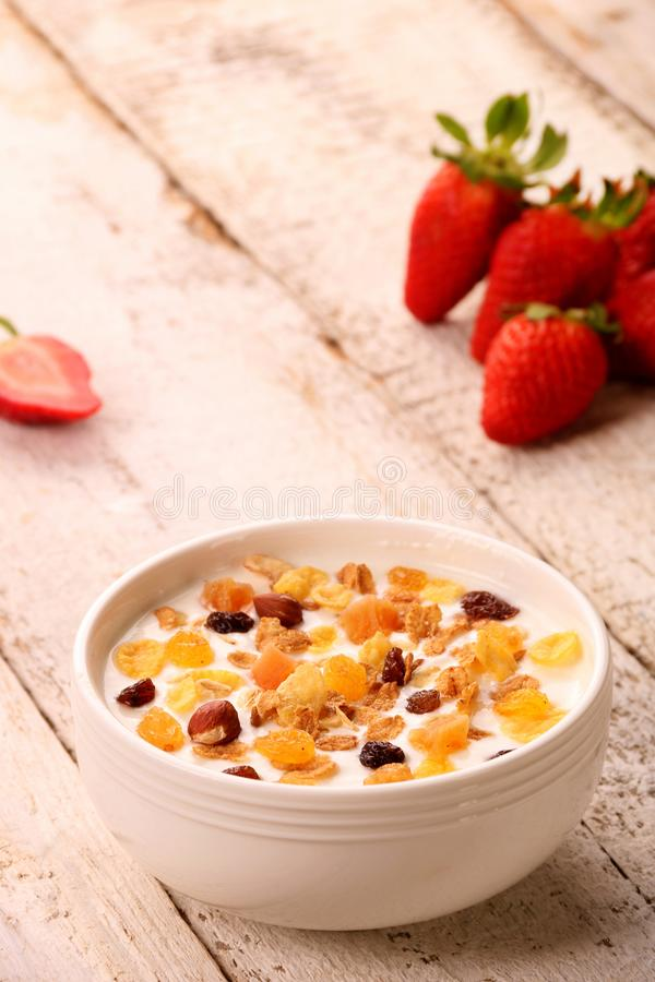 Bowl of yogurt with strawberries and granola muesli, over a white wood background stock photo