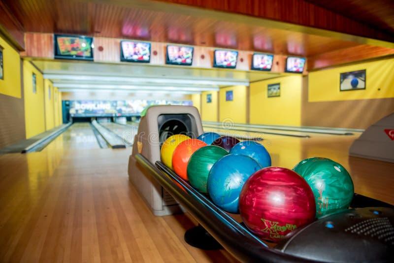 Bowla centrerar färgade bollar i linje i en bowling royaltyfri bild