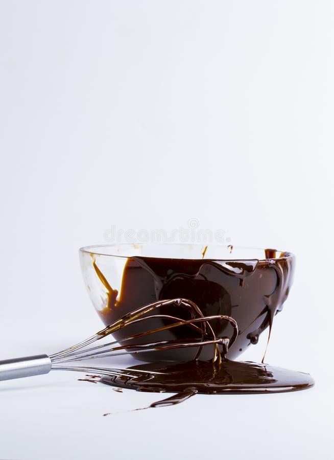 bowla med chokladen och flytandechoklad på vit bakgrund royaltyfri foto