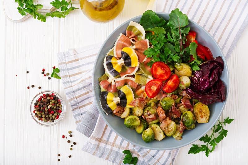 Bowla med Farfalle pasta, Bryssel groddar med bacon och sallad för ny grönsak arkivfoton