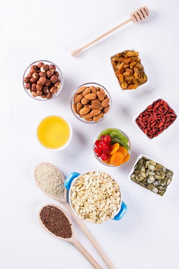 Bowla med ingredienser för att laga mat hemlagad granola på vit bakgrund Sund snak royaltyfri bild