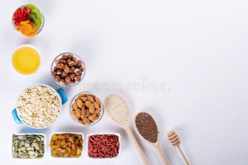 Bowla med ingredienser för att laga mat hemlagad granola på vit bakgrund Sund snak arkivfoto