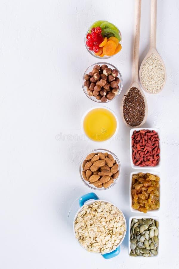 Bowla med ingredienser för att laga mat hemlagad granola på vit bakgrund Sund snak arkivbilder