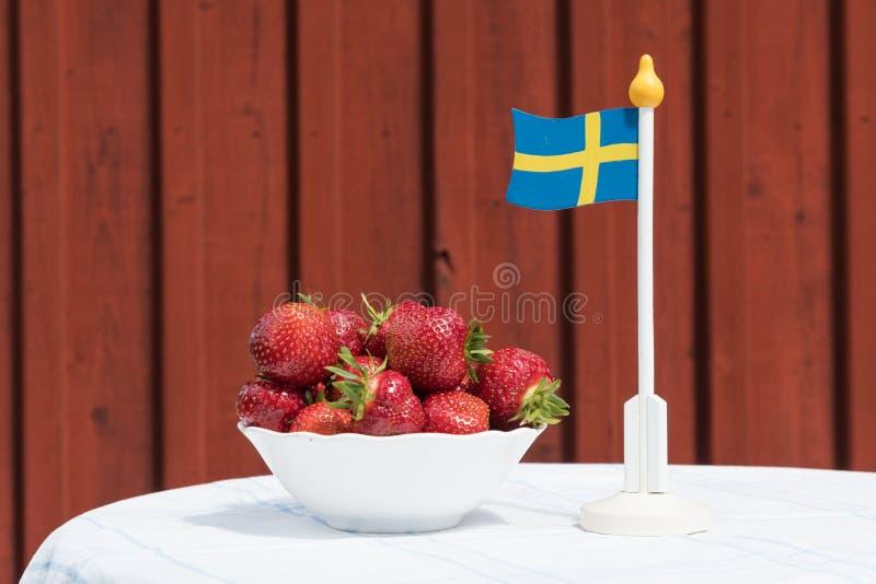 Bowla med nya jordgubbar och en svensk flagga fotografering för bildbyråer