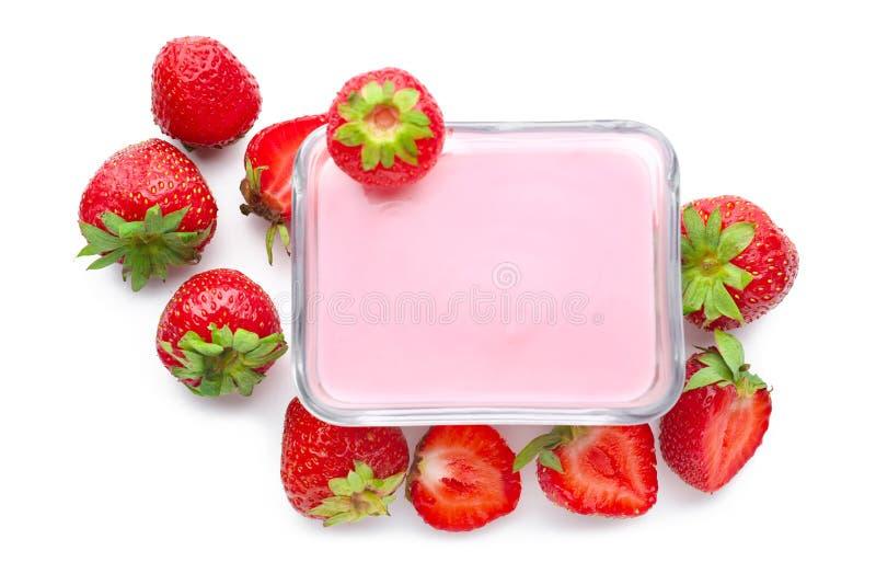 Bowla med smaklig yoghurt och jordgubbar p? vit bakgrund arkivfoto