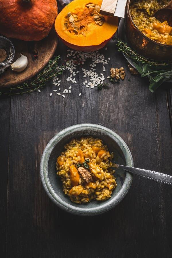 Bowla med vegetarisk den pumparisotto och skeden på mörk lantlig köksbordbakgrund med matlagningingredienser, bästa sikt Sunt arkivfoto