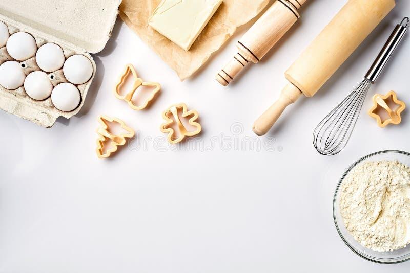 Bowla med vetemjöl, kavel, vifta, ägg, smör, kakaskärare Bästa sikt på en vit tabell med ett kopieringsutrymme arkivbild