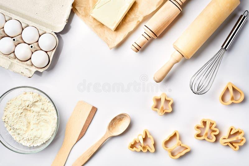 Bowla med vetemjöl, kavel, vifta, ägg, smör, kakaskärare Bästa sikt på en vit tabell med ett kopieringsutrymme arkivfoton