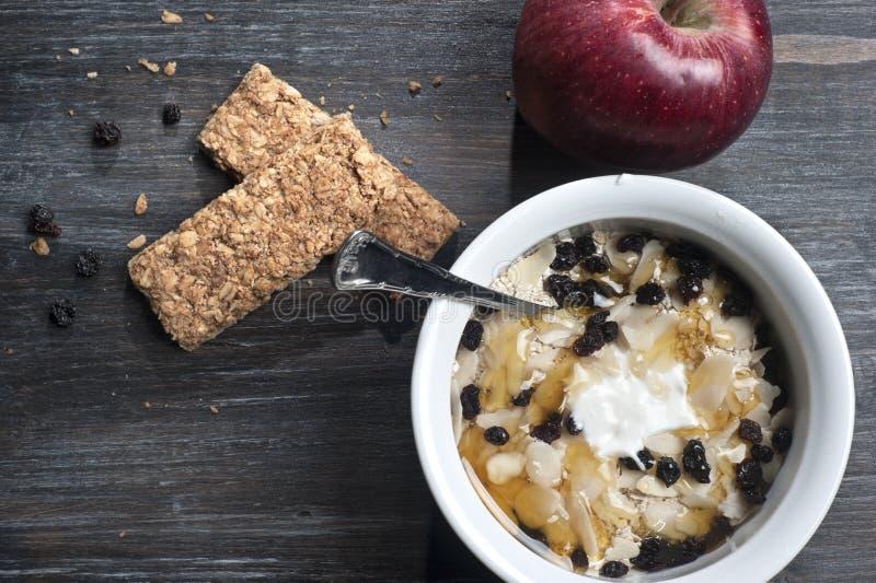 Bowla med yoghurt, mysli och honung på golv royaltyfria bilder