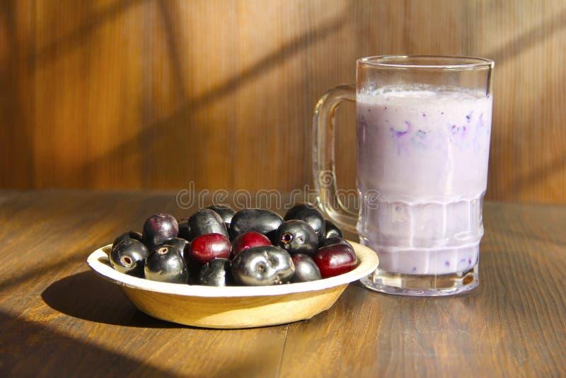 Bowla mycket av Jamun frukt eller svärta plommonet tillsammans med milkshake av samma royaltyfri bild