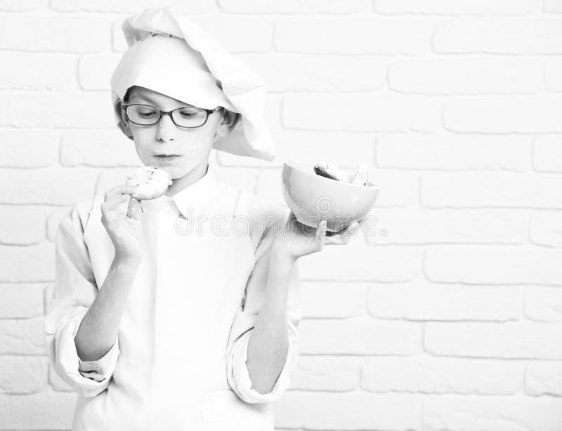 Bowlar den gulliga kockkocken för den unga lilla pojken i den vita likformign och hatten på nedfläckat framsidamjöl med exponerin arkivfoto